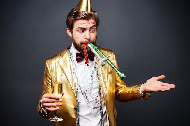 Удивленный мужчина с вентилятором, стоящим с бокалом шампанского