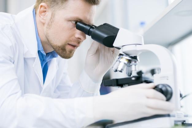 Удивленный микробиолог смотрит на микроскоп окуляра