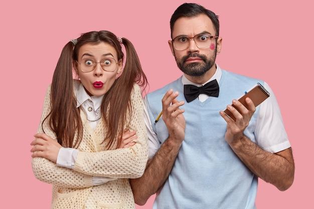 놀란 괴짜 부부는 분개 한 표정으로 응시하고, 나쁜 소식을 듣고, 나선형 메모장에 메모를 작성합니다.