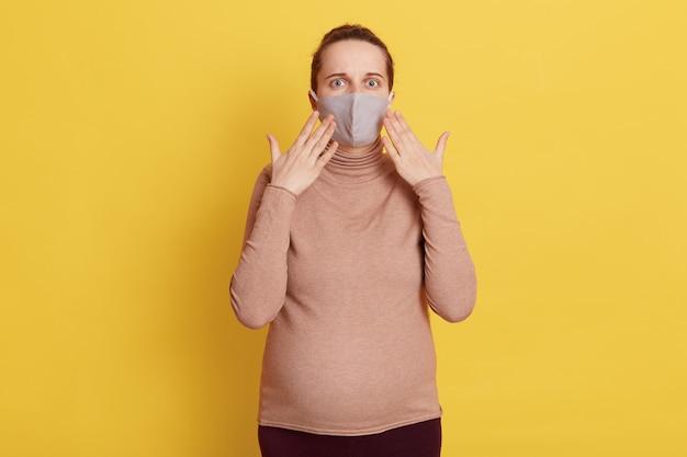 Удивленная беременная женщина в повседневной одежде и медицинской маске, испуганная и шокированная, держа ладони у лица, изолированной желтой стеной.