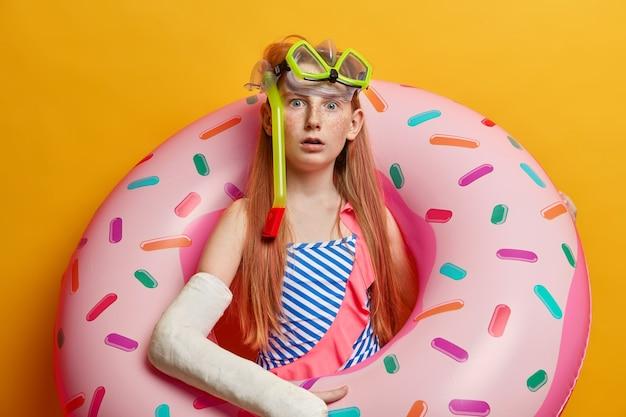 Удивленная рыжая девушка с веснушками позирует с надутым кольцом, носит купальник и маску для подводного плавания, потрясена аварией в море, получила травму и травму во время отдыха, сломала руку в гипсе Бесплатные Фотографии