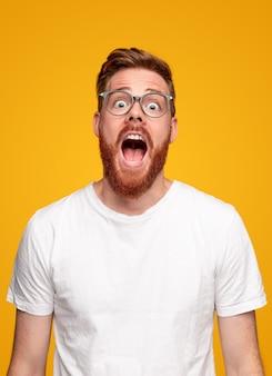 Удивленный рыжий мужчина с бородой смотрит в камеру и громко кричит на желтом фоне