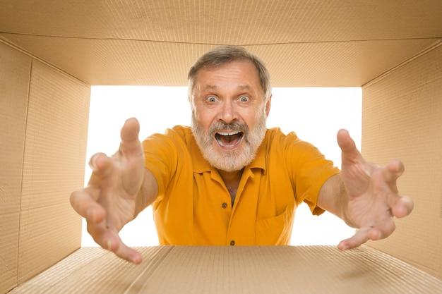 Uomo anziano stupito che apre il più grande pacchetto postale isolato su bianco. modello maschio felice sopra la scatola di cartone che guarda dentro.