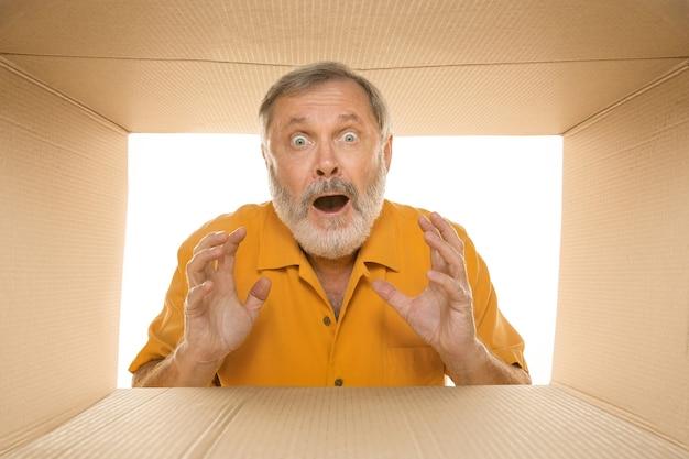 Uomo anziano stupito che apre il più grande pacchetto postale isolato su bianco. felice modello maschile sopra una scatola di cartone