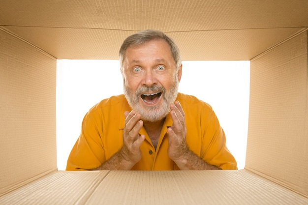 Удивленный старший мужчина открывает самый большой почтовый пакет, изолированный на белом. счастливая мужская модель поверх картонной коробки