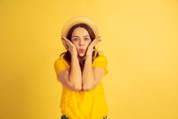 놀랐고, 놀랐고, 귀엽다. 노란색 스튜디오 배경에 백인 여자의 초상화입니다. 모자에 아름 다운 여성 모델입니다. 인간의 감정, 표정, 판매, 광고의 개념. 여름철, 여행, 리조트.