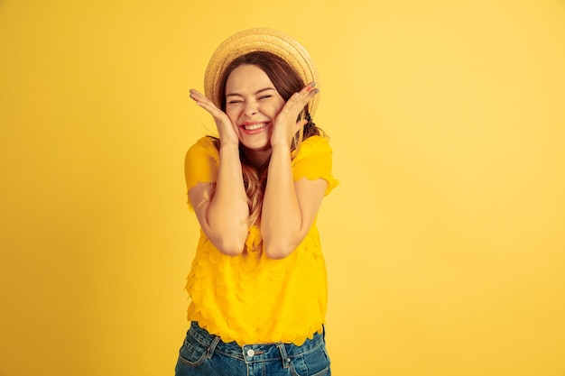 Astonished, shocked, cute. caucasian woman's portrait on yellow studio background. beautiful female model in hat. concept of human emotions, facial expression, sales, ad. summertime, travel, resort.