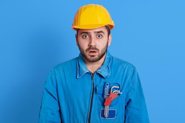 黄色いヘルメットと青いユニフォームを着て、口を開けて大きな目を見て驚いたショックを受けた若い無精ひげを生やしたビルダーは、色の壁に対して、ポケットに道具を持っている、何か衝撃的なものを見ます。
