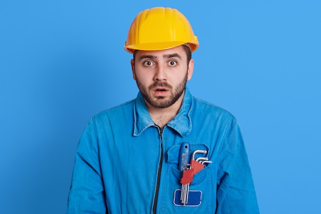 Astonished shocked young unshaven builder wearing yellow helmet and blue uniform, staring with mouth opened and big eyes, sees something shocking, having tool in pocket, against color wall.