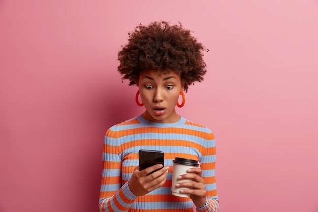 Astonished surprised curly young woman stares at smart phone display, sees something amazing online, reads disturbing insulting message, drinks takeout coffee, poses against pink wall.