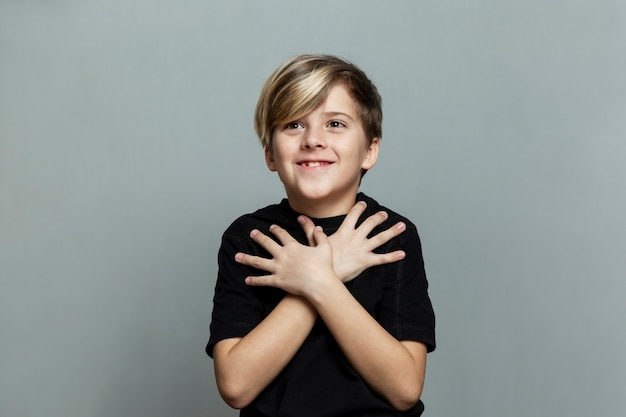 Astonished and surprised smiling boy with a fashionable hairstyle in a black t-shirt
