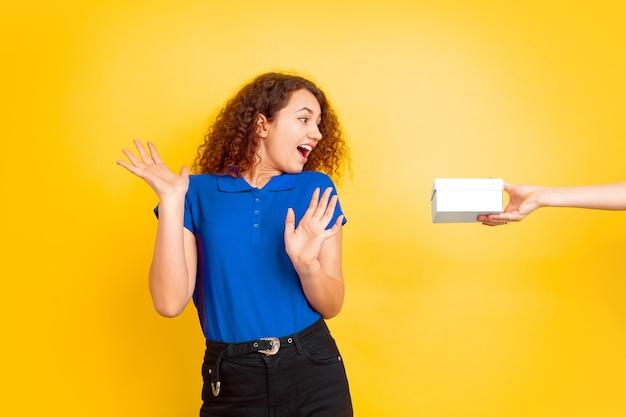 Stupito prendendo una confezione regalo. ritratto della ragazza dell'adolescente caucasico sulla parete gialla. bello modello riccio femminile. concetto di emozioni umane, espressione facciale, vendite, annuncio, educazione. copyspace.