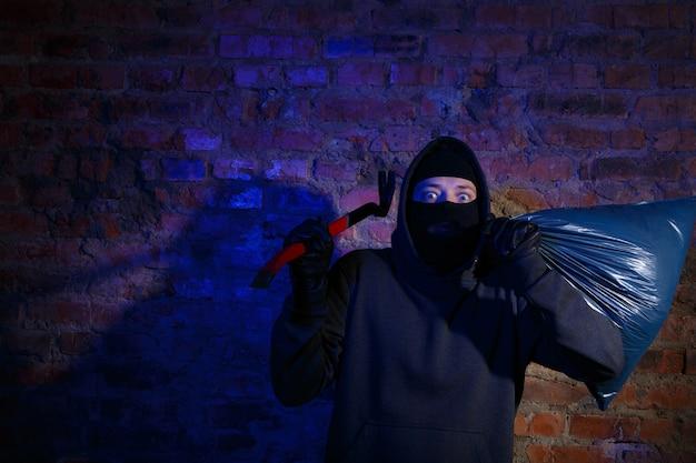 밤에 가방과 마스터 키가 있는 벽돌 벽에 서 있는 놀란 도둑
