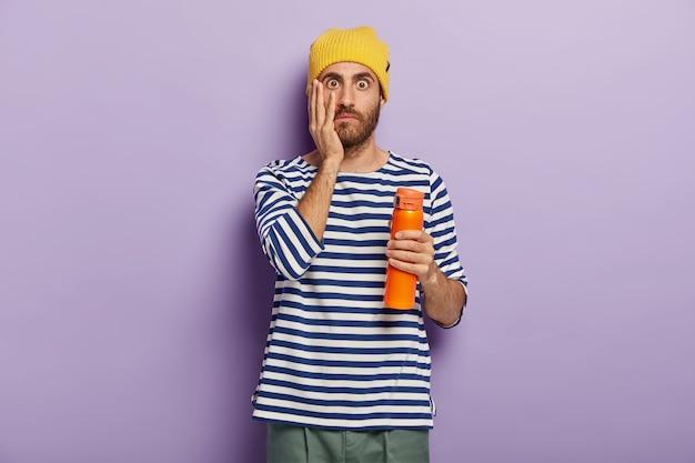 Il turista stupito fa una pausa caffè, tiene la fiaschetta con la bevanda, tocca la guancia, indossa abiti casual, riceve voci inaspettate, isolato su sfondo viola