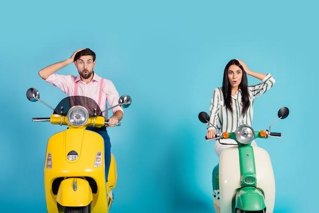 놀란 두 자전거 타는 사람 남자 여자 여행 노란색 녹색 모터 자전거 그들은 잃어버린 믿을 수없는 아이디어를 얻을 감동 터치 손 머리 비명 와우 omg 파란색 벽 위에 절연