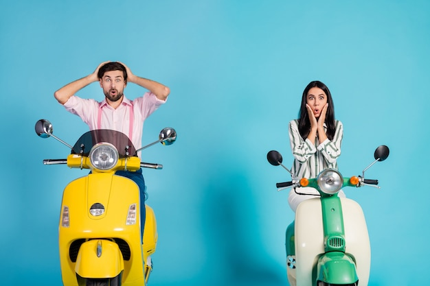 Astonished two bikers ride yellow green electric scooters impressed by idea man woman she he get lost scream omg unbelievable wear formalwear clothes isolated over blue color wall