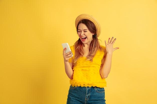 스마트 폰을 사용하여 놀랐습니다. 노란색 스튜디오 배경에 백인 여자의 초상화입니다.