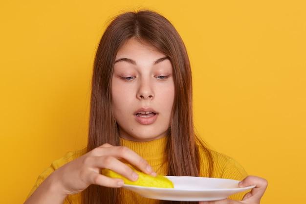 汚れた皿とスポンジを手に持つ驚いた女性は、驚いた表情でポーズをとり、黄色の壁に孤立したスタンド、開いた口を持つ女性、カジュアルな服を着ています。