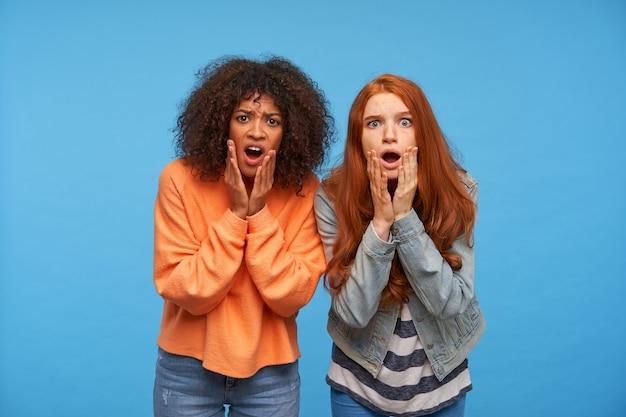 Stupite giovani belle donne che si tengono il viso con le mani alzate mentre guardano sorpresi con la bocca aperta, in piedi contro il muro blu
