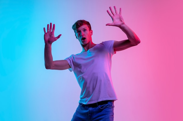 Astonished. young caucasian man's portrait on gradient blue-pink studio background in neon light. concept of youth, human emotions, facial expression, sales, ad. beautiful model in casual.