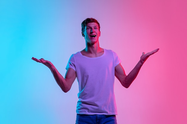 놀랐습니다. 네온 불빛에 그라데이션 블루 핑크 스튜디오 배경에 젊은 백인 남자의 초상화. 청소년, 인간의 감정, 표정, 판매, 광고의 개념. 캐주얼에 아름다운 모델.