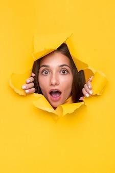 입으로 놀란 젊은 여성이 밝은 노란색 종이에 찢어진 구멍을 들여다 보면서 흥분을 위해 헐떡 거리며 열었습니다.