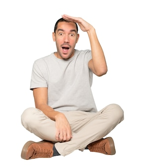 Удивленный молодой человек жестом отводит взгляд