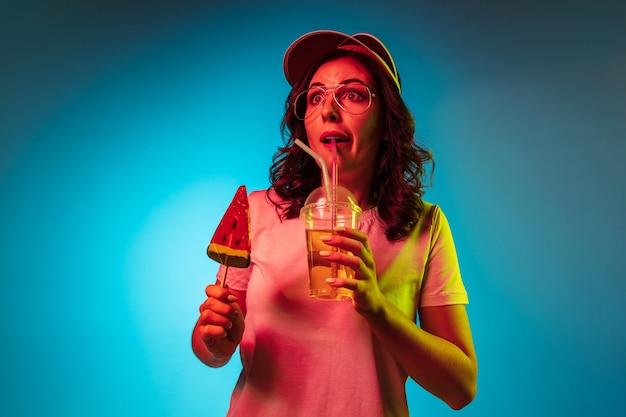 トレンディな青いネオンスタジオでお菓子と飲み物を保持している帽子をかぶった驚いた若い女性