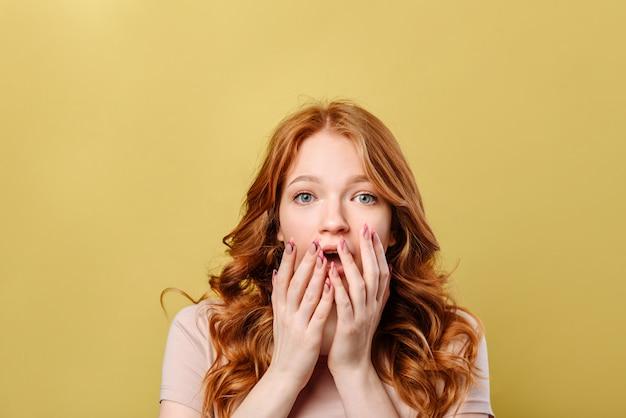 びっくりした若い女性は彼女の手のひらを彼女の口に置きました