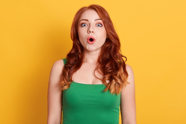 Astonished young woman with wavy red hair  with shocked facial expression, looking at camera with opened mouth against yellow wall