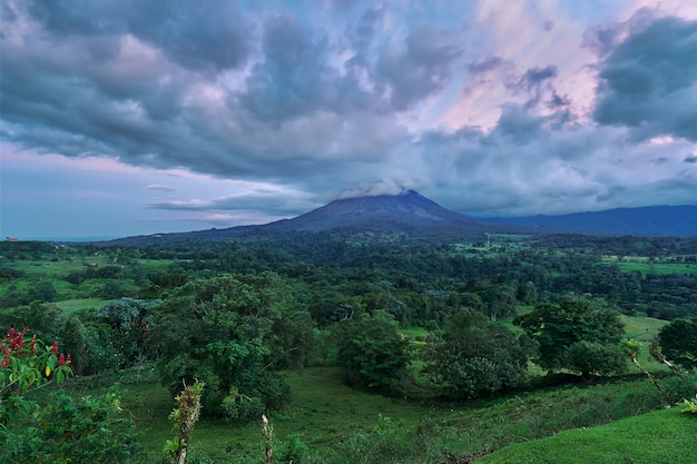 Astonishing panoramic view of the arenal volcano in costa rica after a forest partly covered with clouds during the sunset in a dramatic sky
