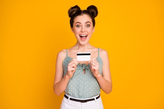 Девушка astonsihed держит кредитную карту, изолированную над желтым