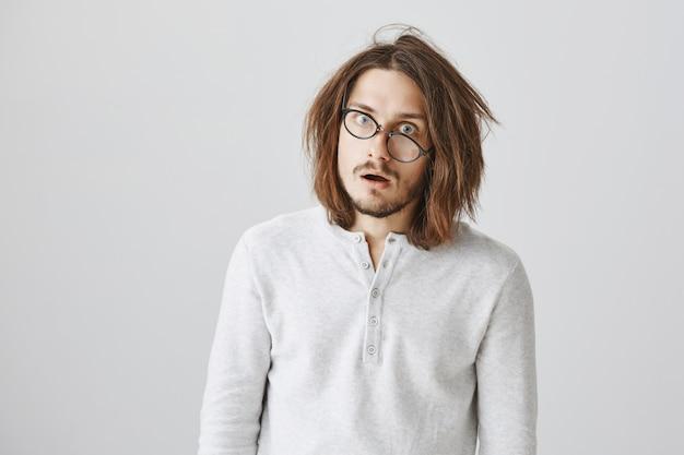 Удивленный и шокированный мужчина с растрепанными волосами впечатлил