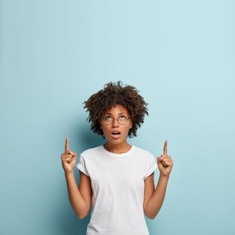 人差し指で上記の驚異的な巻き毛の女性のポイント、興味をそそるプロモーションを読む
