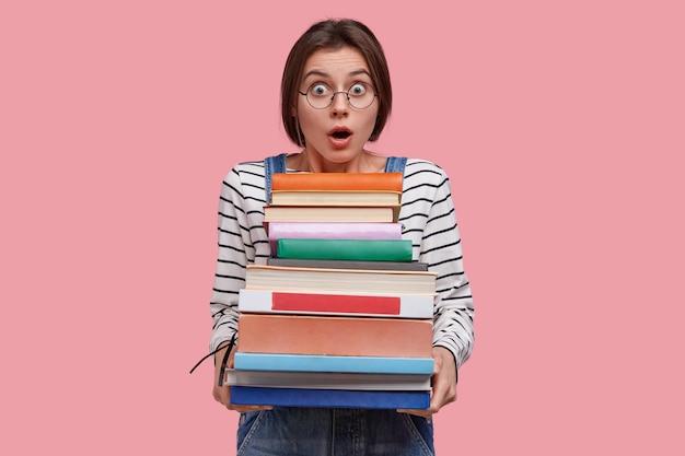 줄무늬 옷을 입고 검은 머리를 가진 놀란 젊은 유럽 여성은 많은 책을 운반합니다.