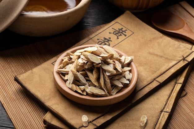 Astragalus membranaceus、テーブルの上の古代漢方薬の本とハーブ。