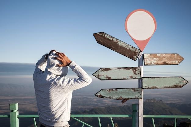 疑わしい迷いの男は、空の道標の前に立って混乱している
