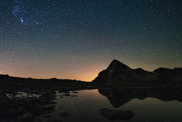 Astro starry sky reflected on lake at high altitude on the alps. orion constellation glowing.