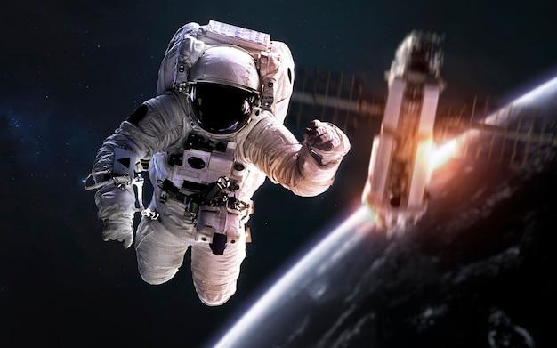 Астронавт на выходе в открытый космос, спутник на орбите планеты земля. элементы этого изображения, предоставленные наса