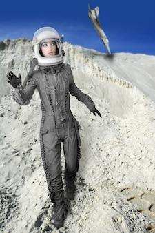 Astronaut fashion womanaircraft crash space suit helmet moon landscape