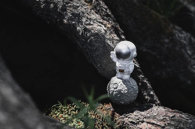 石の間に宇宙飛行士の置物が立っています