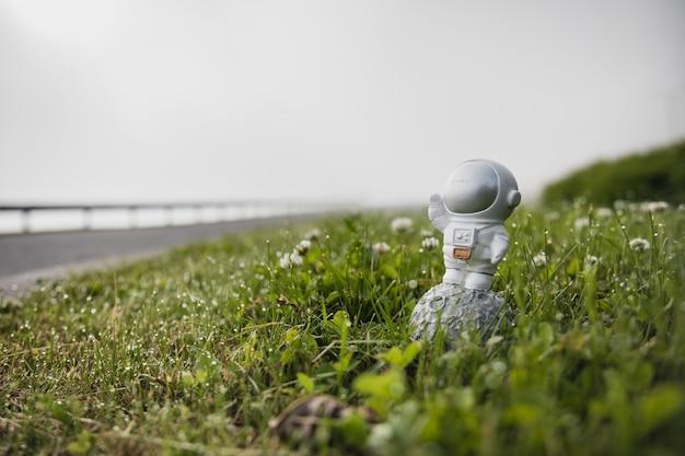 宇宙飛行士の置物は緑の芝生の上に立っています