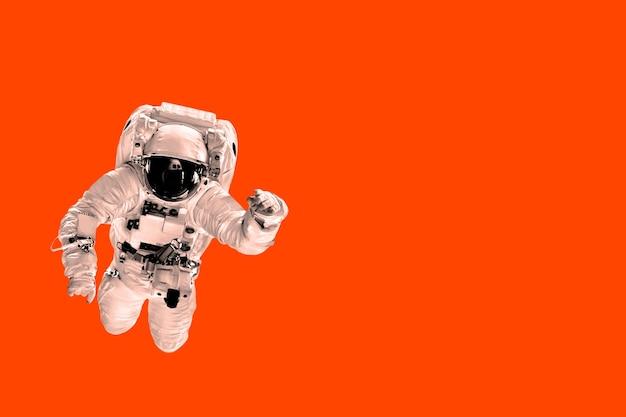 Астронавт пролетает над трендом цвета пышной лавы.