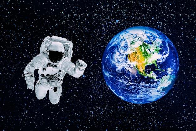 Астронавт пролетает над землей в космосе. элементы этого изображения предоставлены наса