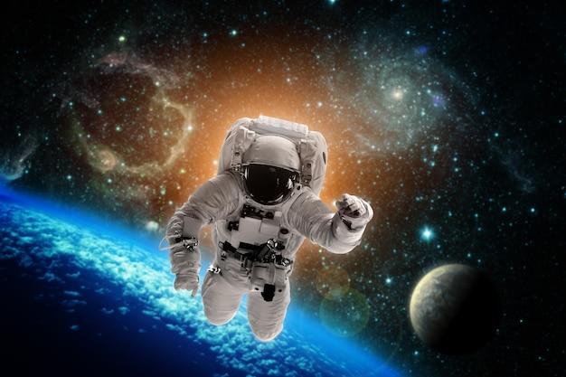 宇宙飛行士は宇宙で地球上空を飛行します。 nasaによって提供されたこの画像の要素