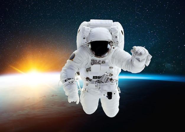 놀라운 일몰과 별이 있는 푸른 행성 지구의 배경에서 우주를 비행하는 우주 비행사. 임무를 수행하고 우주 공간에서 부상하는 우주인