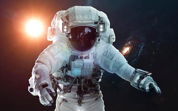 Астронавт в глубоком космосе. символ освоения космоса. элементы этого изображения, предоставленные наса