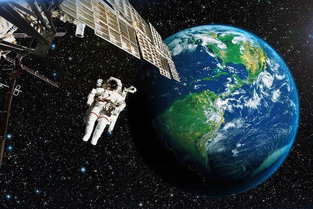 Астронавт в космическом пространстве на фоне планеты земля.