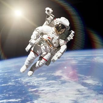 地球を背景に宇宙空間にいる宇宙飛行士