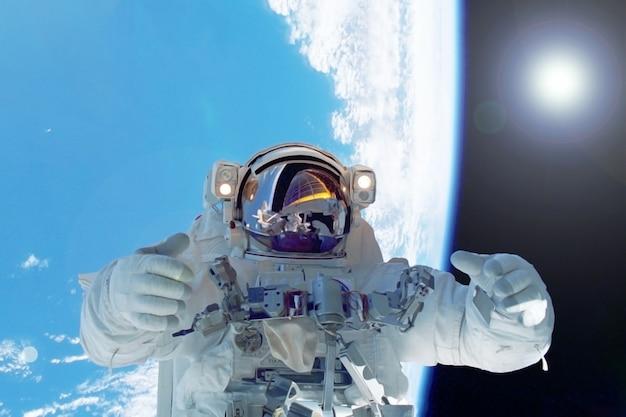 地球を背景にした宇宙飛行士nasaから提供されたこの画像の要素